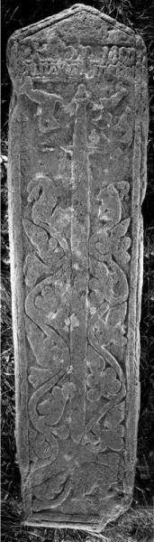 A black and white photograph of a long and narrow grave slab decorated with carvings of beasts in relief