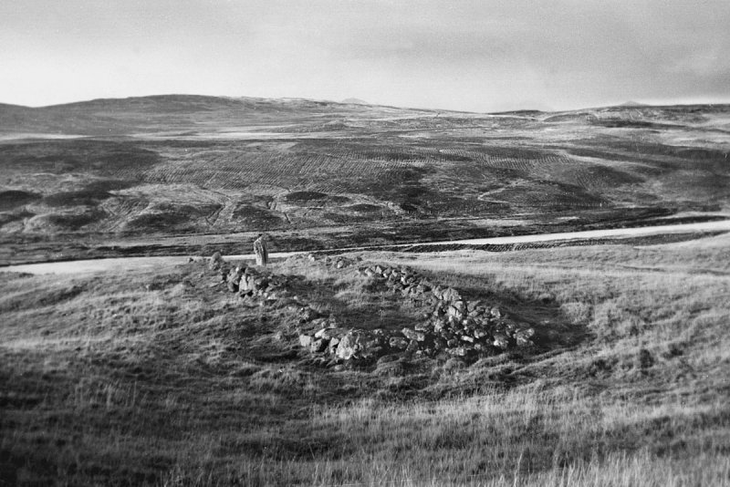 A black and white showing a person standing beside the remains of a rectangular structure in an upland location
