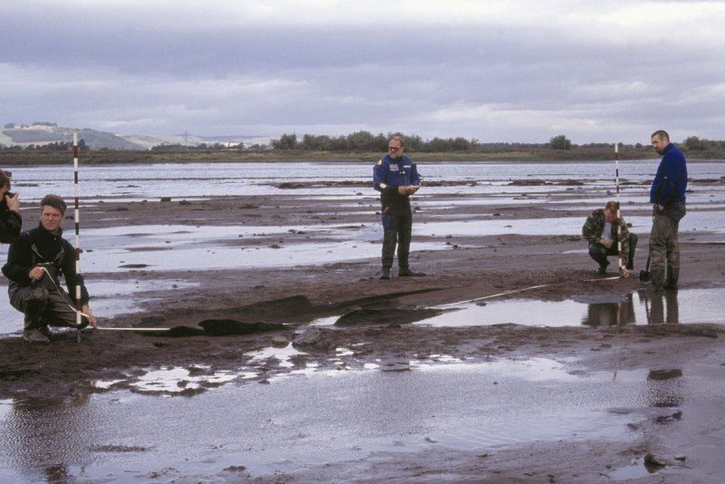 A photograph showing four people surveying the remains of a boat on the seashore