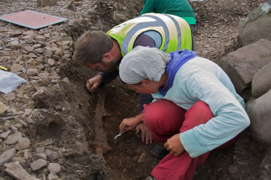 A photograph of an archaeological excavation showing two people crouched down carefully excavating with picks