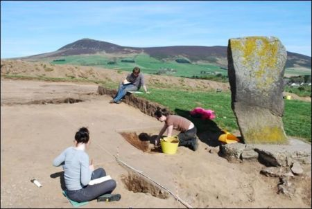 A photogograph of an archaeological excavation showing people excavating beside a large upright stone with Pictish carvings
