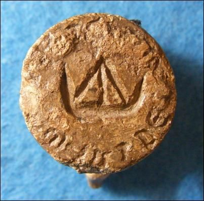 A photograph of a round stamp carved with text around the edge and a ship in the centre