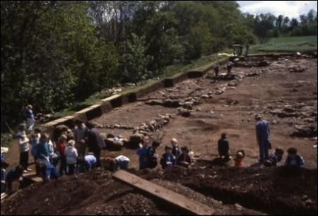 A photograph of an archaeological excavation showing a number of visitors on a site visit with the excavated remains of several rectangular structures in the background