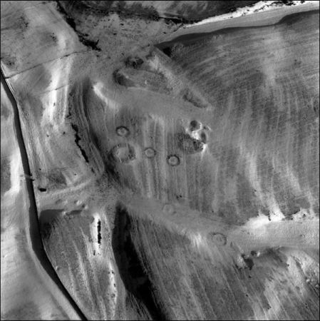 A black and white aerial photograph showing a landscape covered with linear furrows and the scattered remains of circular structures