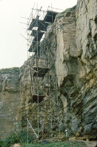 A photograph of scaffolding against a cliff edge and a person wearing a hard hat