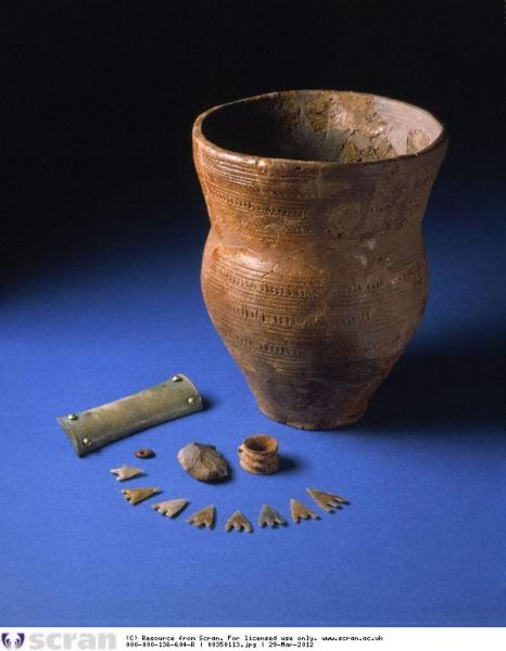 A photograph showing a decorated pot with a flared top and contents including 8 barbed and tanged flint arrowheads, a rectangular stone wrist guard, and an amber bead, arranged beside it