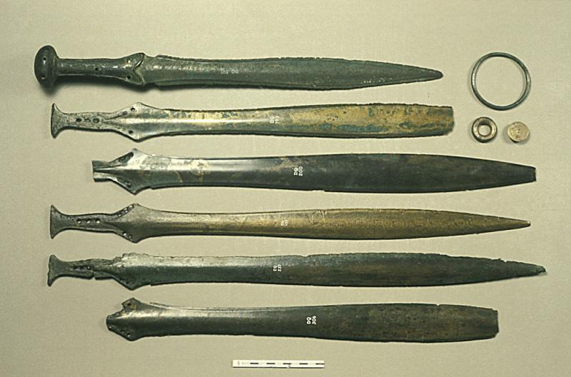 A photograph showing a row of six mostly intact Bronze Age swords, a bronze hoop, a smaller flattened ring, and a small disc