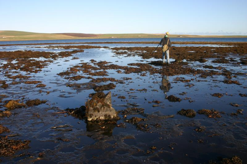 A photograph of a person standing at the sea shore carrying out a survey with GPS equipment