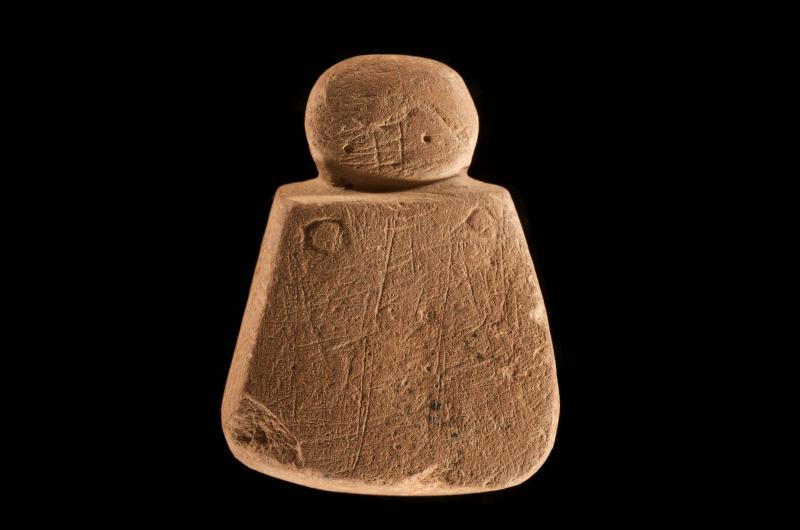 A photograph of a carved stone object shaped like a figure decorated with linear incisions