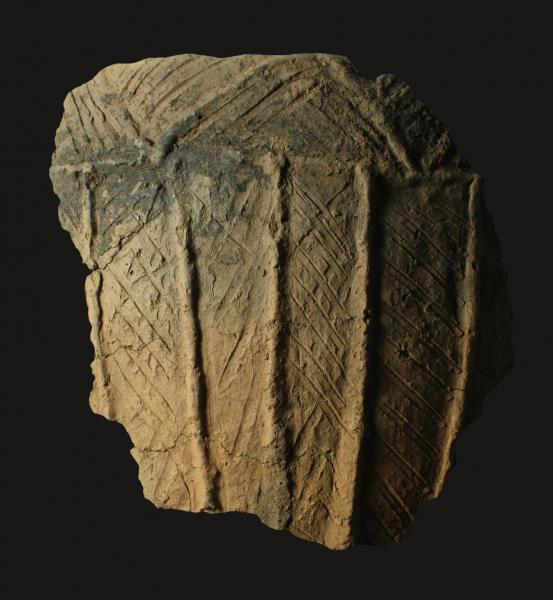 A photograph of a large fragment of pottery decorated with vertical grooves and incised with horizontal lines on the body and v shaped lines around the rim
