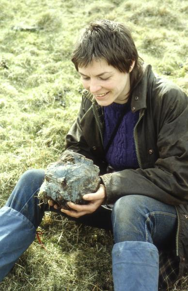 A photograph of a person sitting on grass smiling looking at a large lump of stone