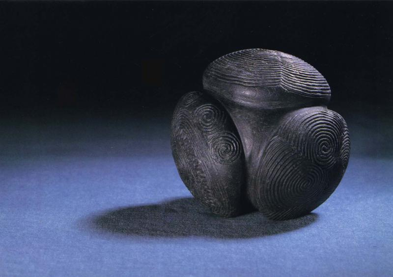 A photograph of a carved stone ball with swirling decoration from Towie in Aberdeenshire