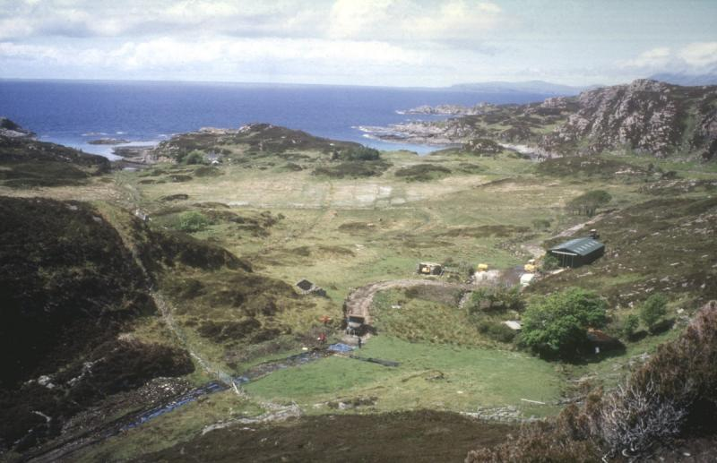 A photograph taken from an elevated position looking down on the excavation site at Camas Daraich and the wider landscape and seascape