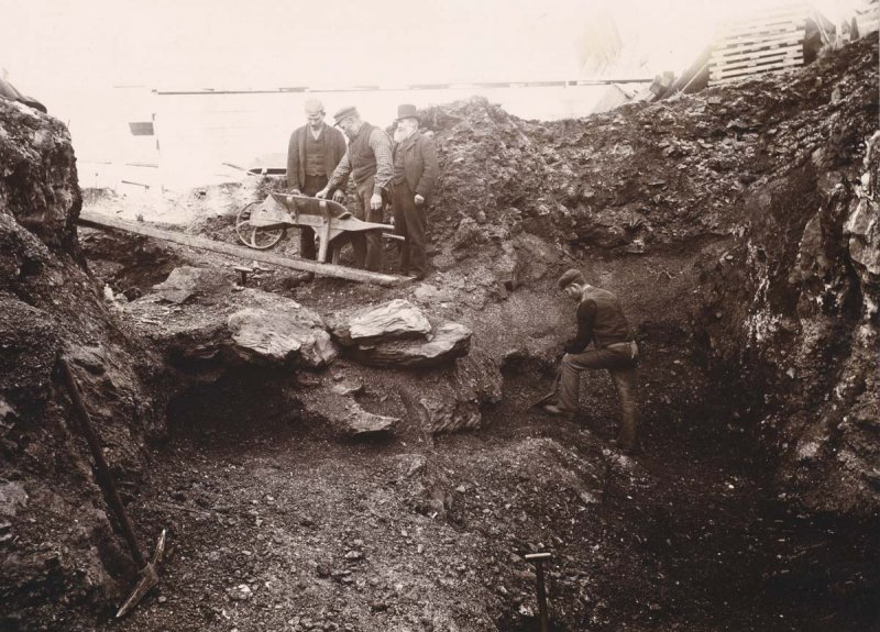 An old sepia photograph of a deep excavation showing a man excavating and three men standing on a ramp with a wheelbarrow
