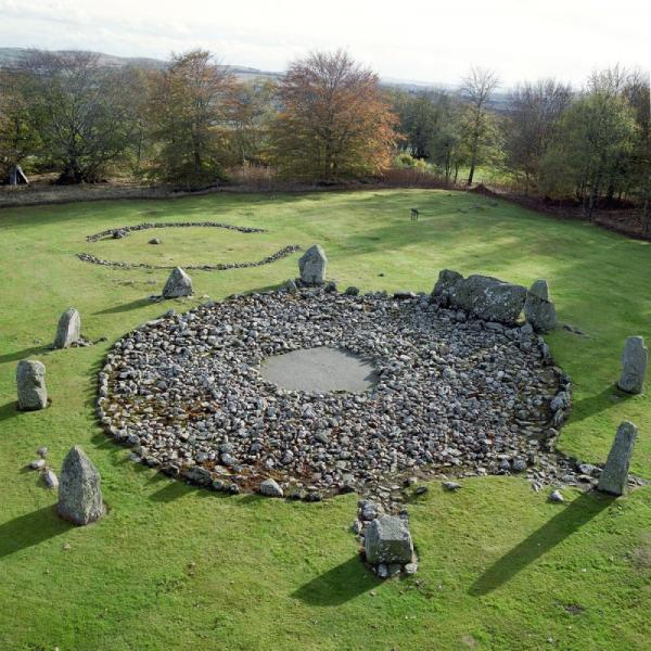 An oblique aerial image showing the stony base of a large circular cairn surrounded by a recumbent stone and nine standing stones with the remains of another cairn in the background, in a field of grass surrounded by trees