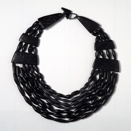 A photograph of a necklace of jet beads with 7 strings and 4 decorated spacer plates narrowing to triangular decorated plates and a triangular bead and loop fastener