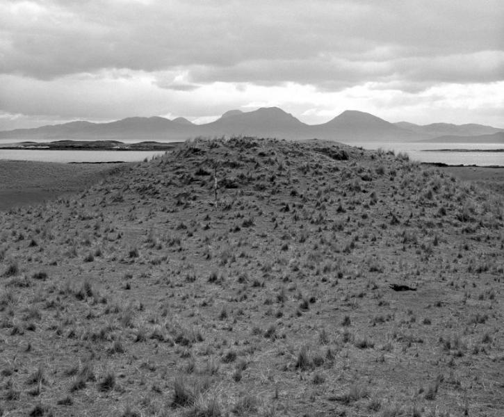 A photograph of a large mound approximately four metres in height with sea and mountains in the background