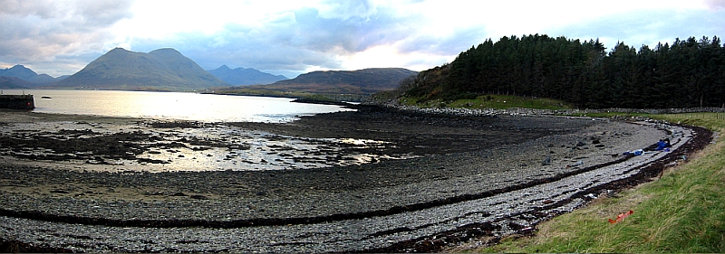 A landscape photograph showing a curved pebbled beach, water and with trees and mountains in the background