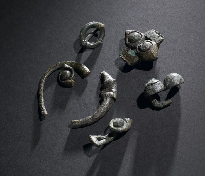A photograph of 6 pieces of decorative metalwork of different shapes and sizes