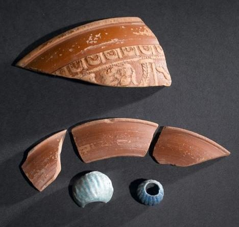 A photograph showing four sherds of Roman samian ware, a blue ribbed bead and a fragment of a larger light blue ribbed bead