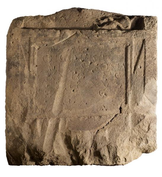 A photograph of a degraded square stone with the faint remains of carved decoration and a Latin inscription