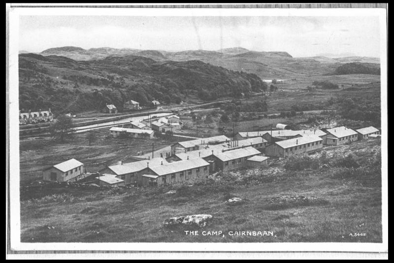 A black and white postcard showing a cluster of long and low rectangular camp buildings set within an upland landscape of rough ground and rock outcrops