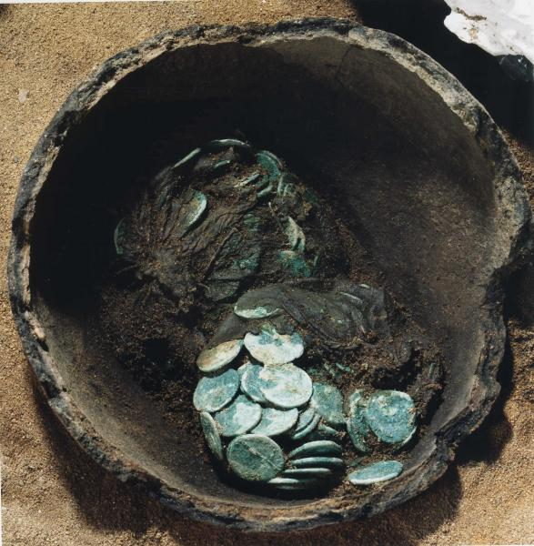 A photograph of an excavated broken ceramic pot containing two clusters of corroded coins with some very degraded organic remains