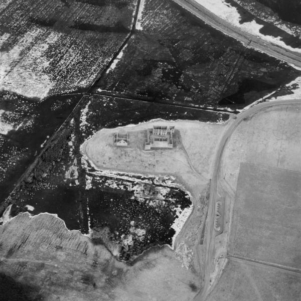 A black and white aerial photograph showing a complex of ruined remains on a prominent mound comprising two large three-storey blocks occupying two sides of a large enclosure and a substantial stable block