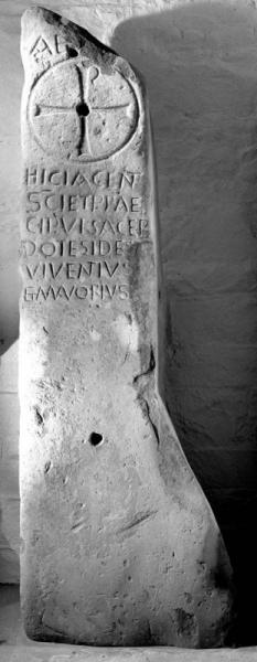 A balck and white photograph of a large upright stone carved with a Latin inscription and ornate cross within a circle