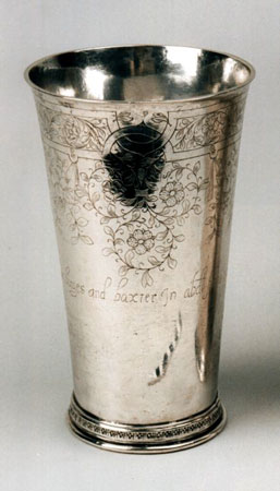 A photograph of a fluted silver beaker with floral engravings