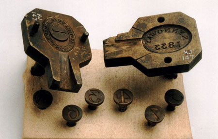 A photograph showing the front and back parts of a token mould and smaller numbered stamps