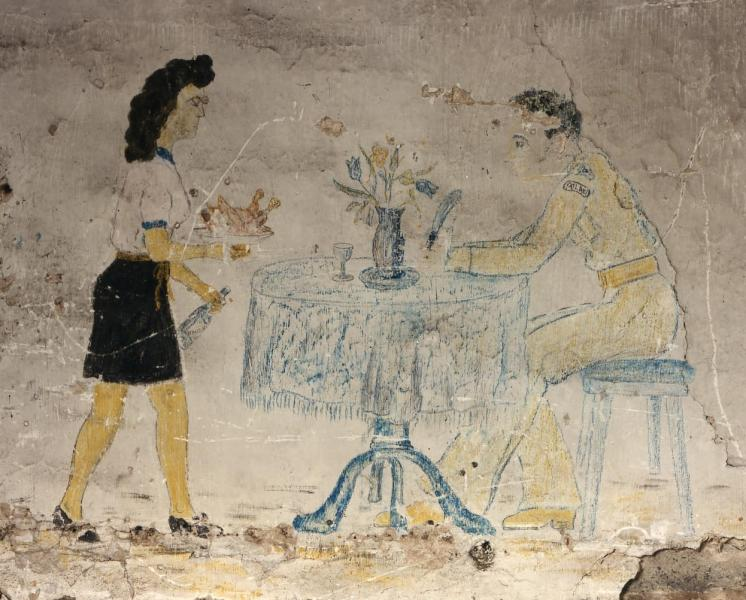 A photograph of painted graffiti showing a man in uniform sitting at a table being served food by a waitress