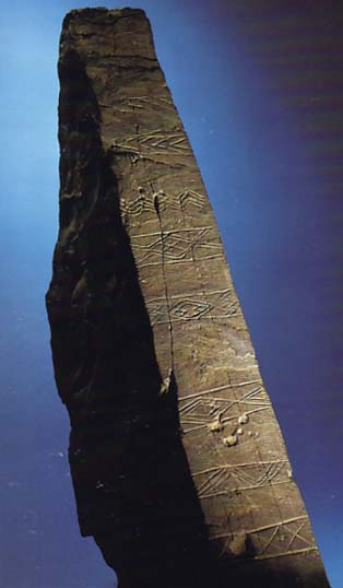 A photograph showing a large decorated stone carved with lines, diamonds and crosses