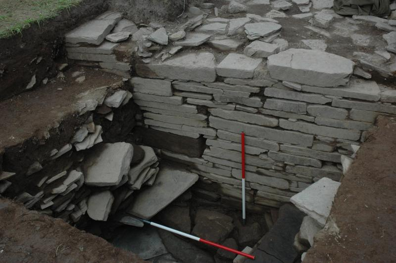 A photograph showing an excavated wall built of slab like stone up to 1.5 metres high