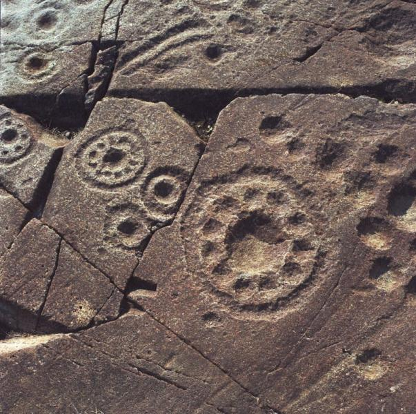 A photograph of flat stone carved with cup marks and elaborate cup and ring motifs