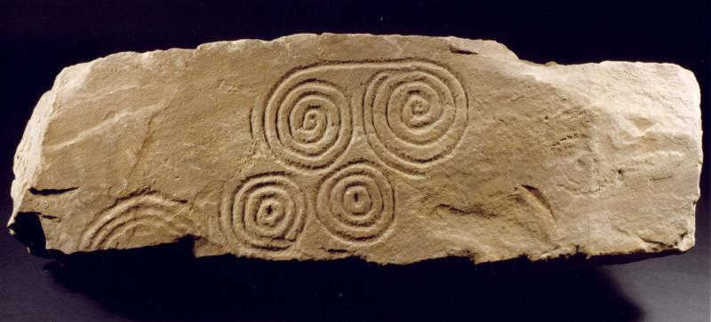 A photograph showing a broken slab decorated with spirals