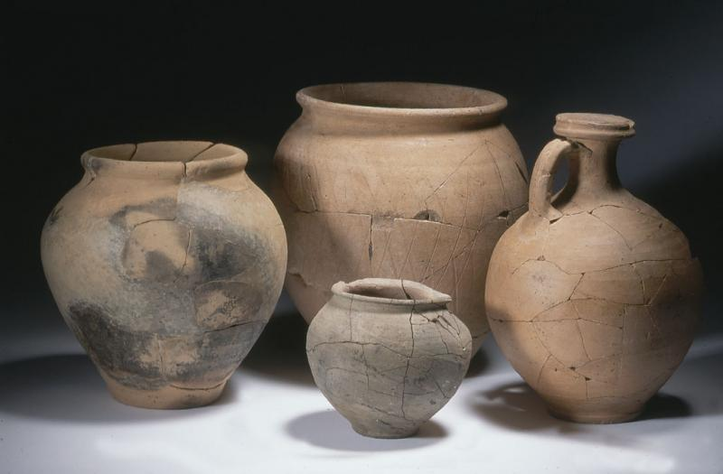 A photograph showing three ceramic pots of different sizes and a rounded jug with a handle