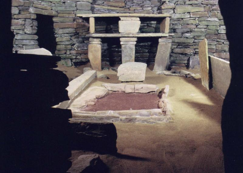 A photograph of the interior of a stone built house showing the stonework, upright stones and large central hearth