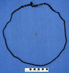 A photograph of a large string with uniformly sized disc jet beads leading to elongated beads at each side towards a toggle fastener