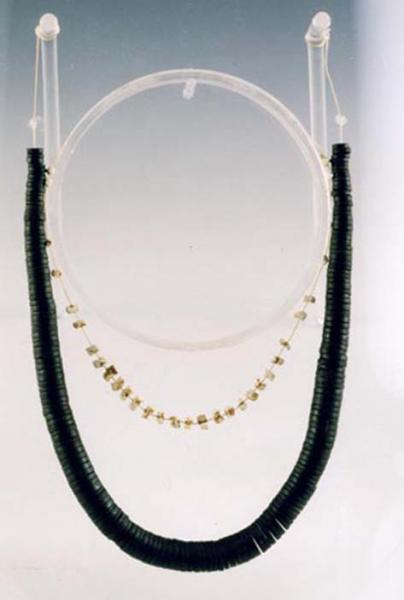 A photograph showing a string of disc shaped jet beads with small beads at the top, becoming wider at the middle with a shorter string of metallic beads attached