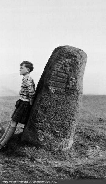 Black and white photo of a boy in a striped jumper and shorts leaning on a standing stone