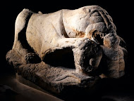 Stone sculpture of a lying lion with a human figure in its front paws and mouth