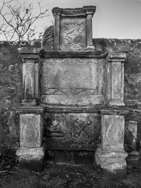 A black and white photo of a large carved stone monument set against a wall