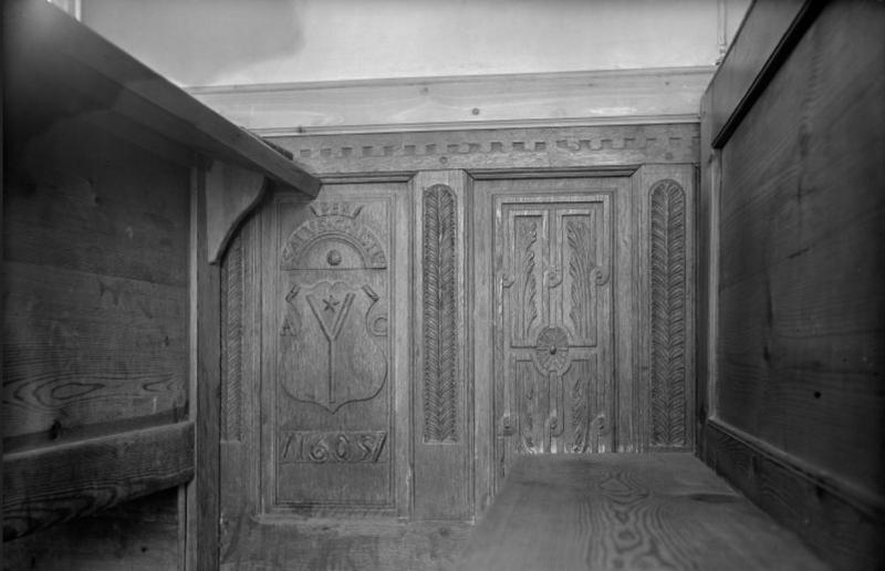 A black and white photo of a carved wooden panel showing a shield and foliate designs