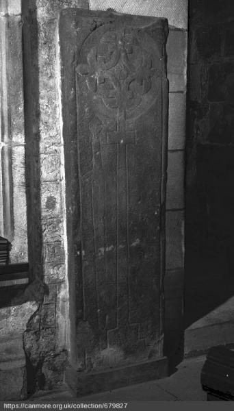Black and white photo of dark stone rectangular cross slab leaning against a wall inside a building