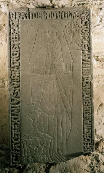 Colour photo of a slab mounted in a stone wall with incised decoration of a female, with hands clasped and writing around three edges