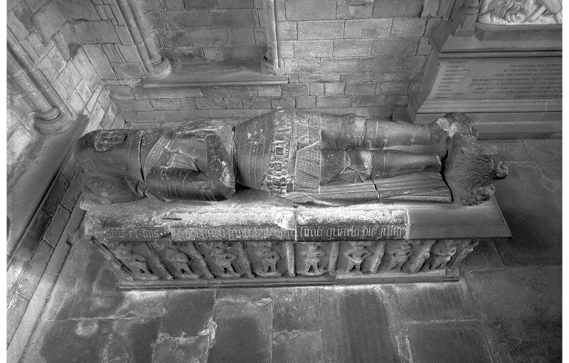 Black and white photo looking down from upon high of a stone tomb with a knighted figure in armour lying on top
