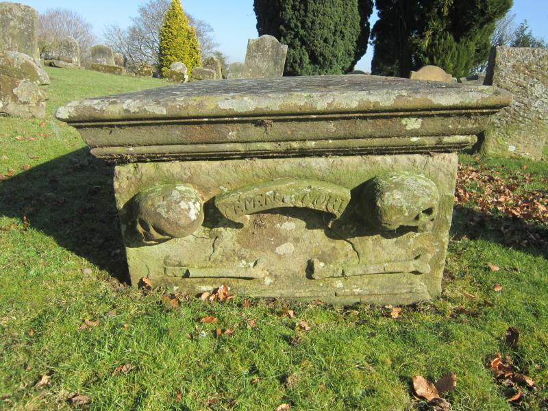 Stone table grave stone with skulls, bones and writing, in a graveyard