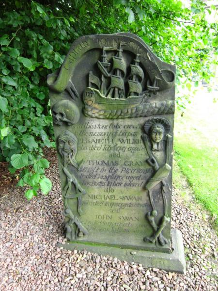 Ornate headstone of a Sea Captain and family, with carvings of a boat, rope, instruments as well as skull and bones