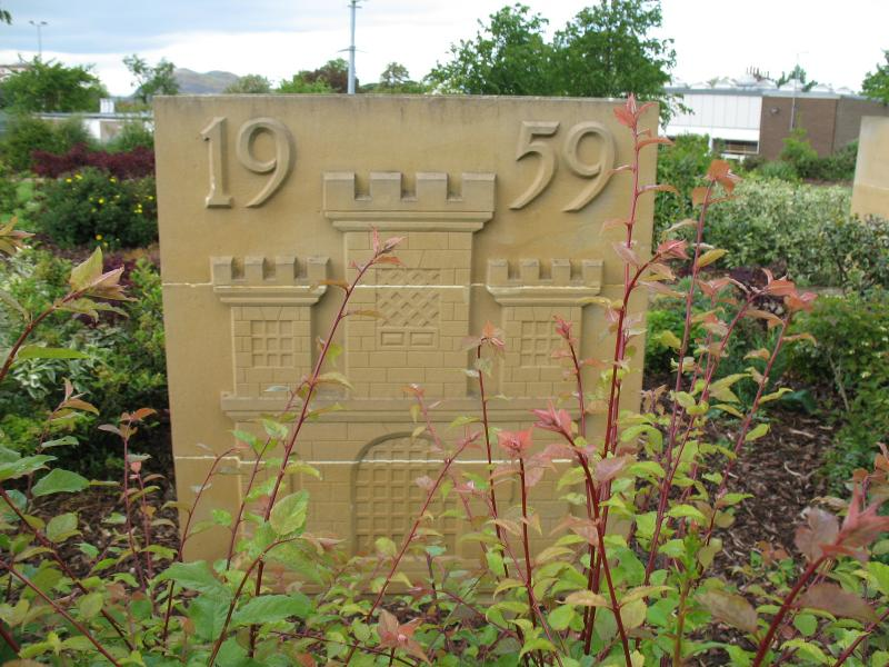 Rectangular yellow stone panel with 1959 and a simplified castle carved into the surface - in a rose garden